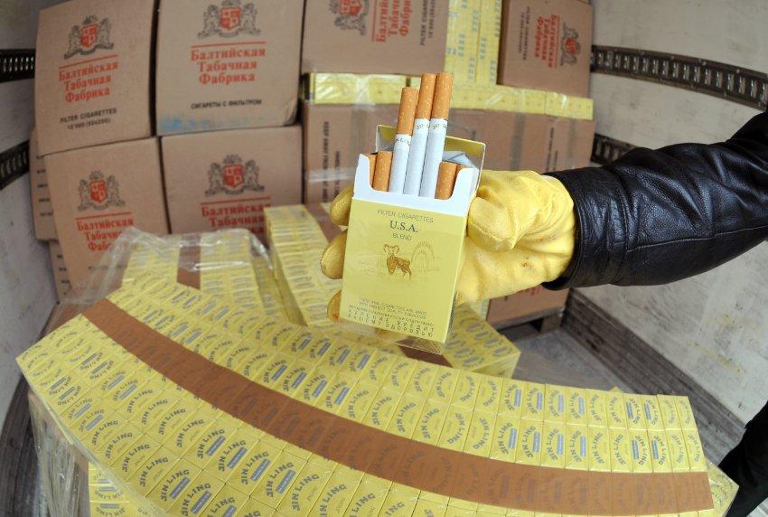 Ein Zollbeamter präsentiert am Freitag (04.04.2008) in Plattling (Niederbayern) geschmuggelte Zigaretten in einem Lastwagen. In Ostbayern ist einer der größten Zigarettenschmuggel-Fälle im Freistaat aufgeflogen. Nach Angaben des Landshuter Hauptzollamtes sind in dem Lastwagen 7,6 Millionen Zigaretten entdeckt worden. Foto: Armin Weigel dpa/lby +++(c) dpa - Bildfunk+++
