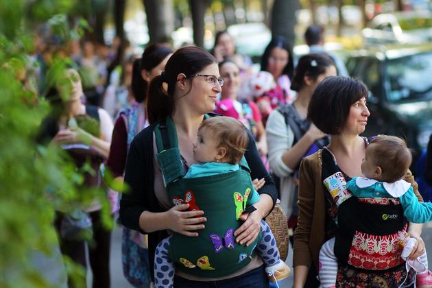 """Mame, care isi poarta copii la piept, participa la un mars organizat cu ocazia evenimentului """"Saptamana Internationala a Purtarii  Bebelusilor"""", in Parcul Copiilor din Timisoara, miercuri, 8 octombrie 2014. SEBASTIAN TATARU / MEDIAFAX FOTO"""