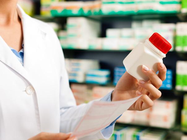 O farmacista cu o cutie de pastile in mana